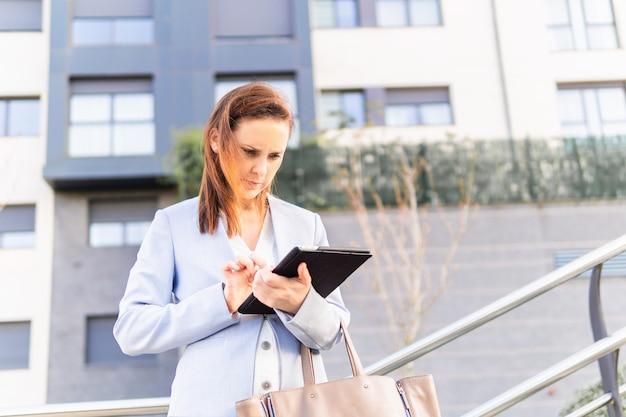 Młoda dorosła kobieta piękna bizneswoman sprawdza biznesową tabletkę. pomyślny biznes kobieta koncepcja. miejsce na kopię. koncepcja biznesowa nieruchomości