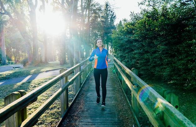 Młoda dorosła kobieta piękny sportowiec trenuje w parku o zachodzie słońca wiosną lub latem koncepcja punktu codzienne szkolenie elitarne szkolenie pielęgnacja osobista