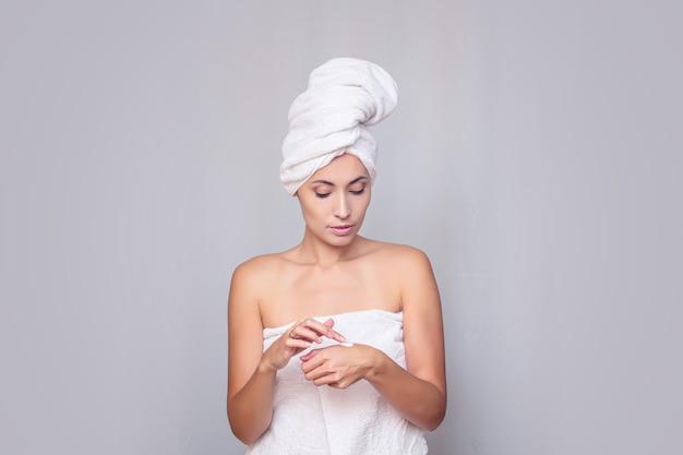 Młoda dorosła kobieta po prysznicu w świeżym ręczniku wykorzystuje fundusze na pielęgnację skóry na odosobnionym tle