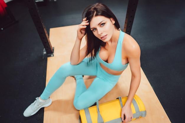 Młoda dorosła kobieta pozuje w gym