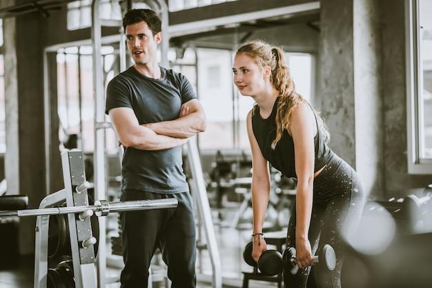 Młoda dorosła kobieta pracująca przy gym