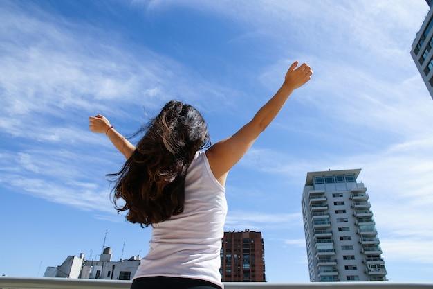 Młoda, dorosła kobieta praktykująca jogę w środowisku miejskim.