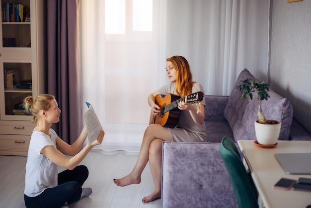 Młoda dorosła kobieta trzyma notatnik muzyczny i patrzy na jej przyjaciela grającego na gitarze. dwie urocze dziewczyny grają muzykę w domu. przyjaźń, miłość, rodzinny wypoczynek, hobby.