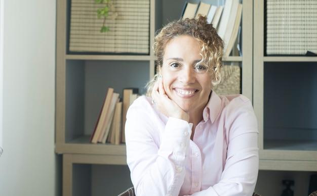 Młoda dorosła kobieta uśmiecha się i patrzy w kamerę siedzącą przy biurku w biurze, pewni ludzie