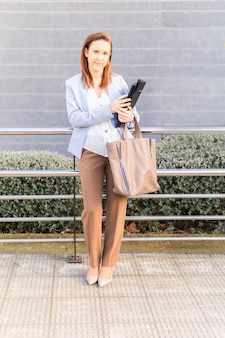 Młoda dorosła kobieta uśmiechnięta piękna bizneswoman czekała na ulicy na klienta z laptopem i folderem. pomyślny biznes kobieta koncepcja. kopiuj przestrzeń