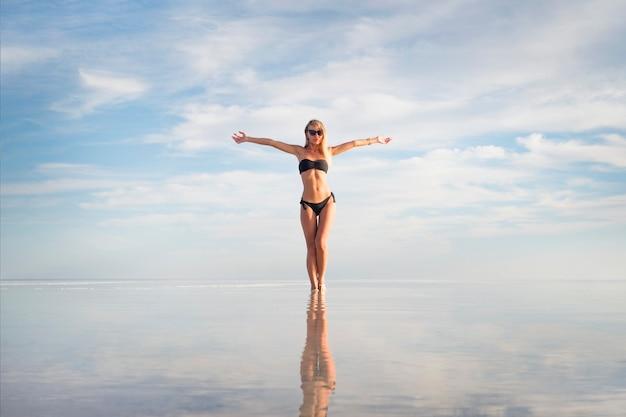Młoda dorosła kobieta w czarny biały strój kąpielowy stojący w wodzie o tekstury wody. słodkie dziewczyny seksualne na tle jeziora lato. niskie białe chmury odbite w czystej wodzie. ręce na bok. boliwia uyuni