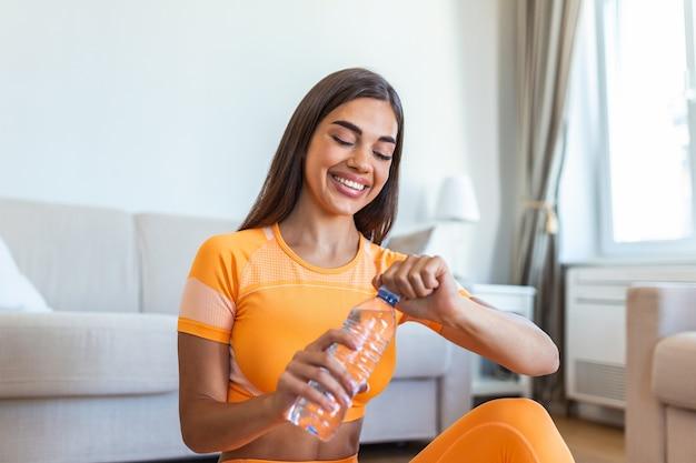 Młoda, dorosła kobieta wody pitnej, siedząc na macie fitness i odpoczynku po treningu w domu