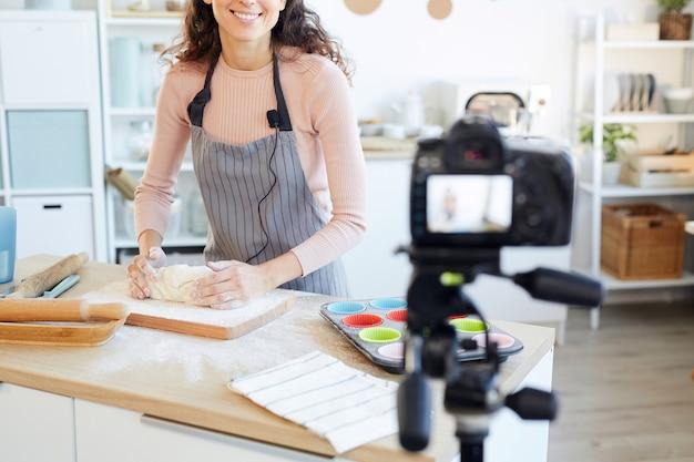 Młoda, dorosła kobieta wyrabiająca ciasto na babeczki podczas kręcenia filmu do swojego bloga kulinarnego