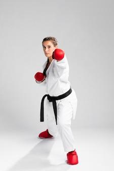 Młoda dorosła kobieta z czarnym pasowym wojownikiem trenuje karate