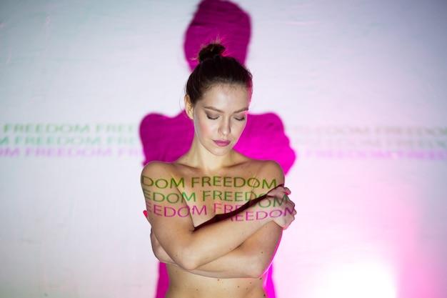 Młoda dorosła kobieta z napisem wolność na swoim ciele