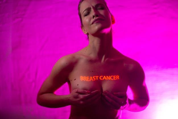 """Młoda dorosła kobieta ze słowami """"rak piersi"""" na piersi ze znamionami"""