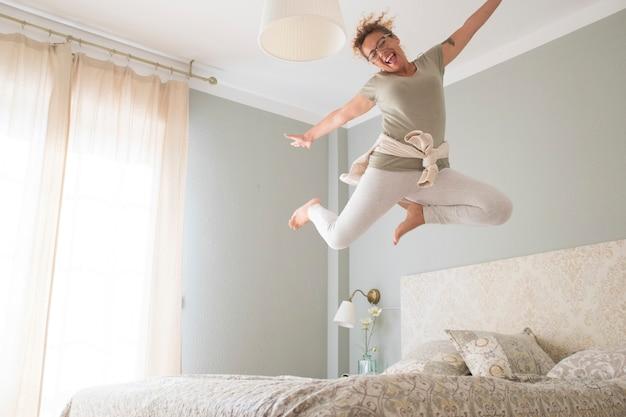 Młoda dorosła ładna kobieta szaleje ze szczęścia i wskakuje na łóżko z filiżanką kawy - rozradowane kaukaskie kobiety same w domu bawią się skacząc w sypialni z szaleństwem