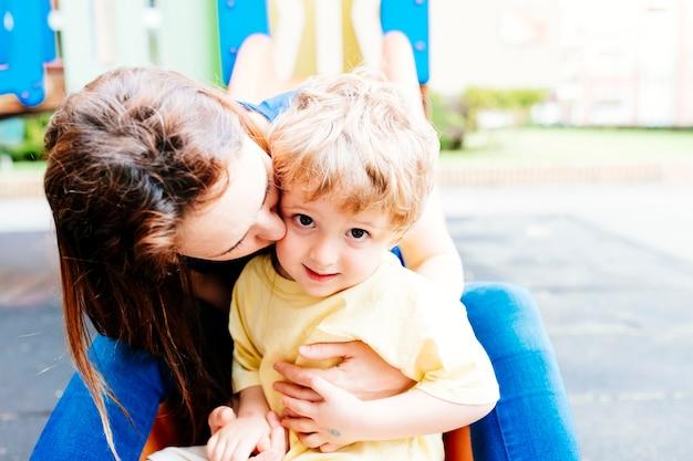 Młoda dorosła matka przytula i całuje swojego trzyletniego syna