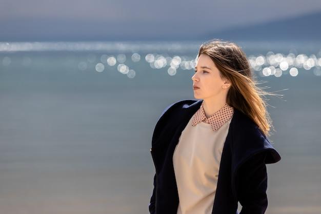 Młoda, dorosła piękna dziewczyna stoi na brzegu na tle zbliżającej się chmury z deszczem