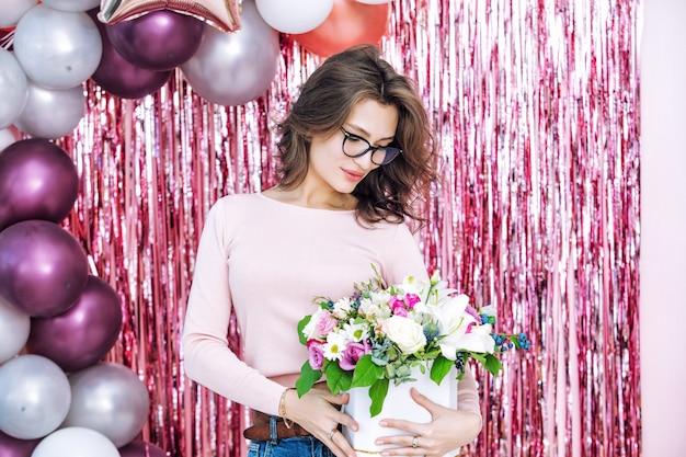Młoda dorosła piękna i szczęśliwa kobieta model trzyma kwiaty portret na świątecznym tle