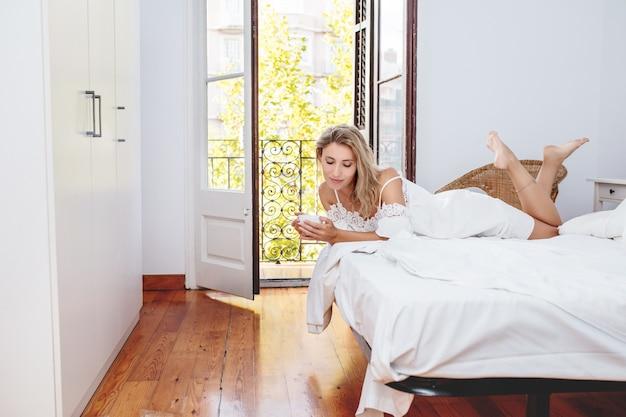 Młoda dorosła piękna kobieta rano w domu w sypialni w białej sukni z filiżanką kawy