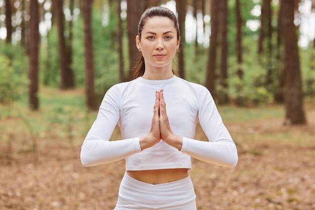 Młoda dorosła skoncentrowana kobieta ubrana w białą sportową górę trzymającą dłonie razem, ćwicząc jogę na świeżym powietrzu w zielonym lesie.
