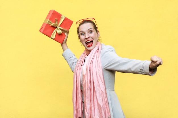 Młoda dorosła szalona kobieta zamachnęła się i chce zrzucić twoje pudełko na prezent na żółtym tle