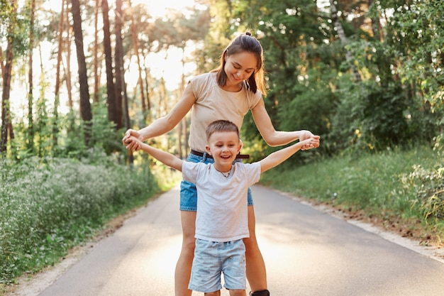 Młoda dorosła szczupła mama z dzieckiem trzymającym ręce dziecka na drogach w parku, rodzina nosząca koszulki i spodenki w stylu casual, spędzająca czas i bawiąca się razem.