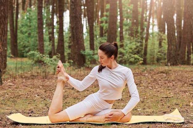 Młoda dorosła urocza ciemnowłosa kobieta z kucykiem trenująca na macie w lesie, rozciągająca nogę, ubrana w stylową odzież sportową