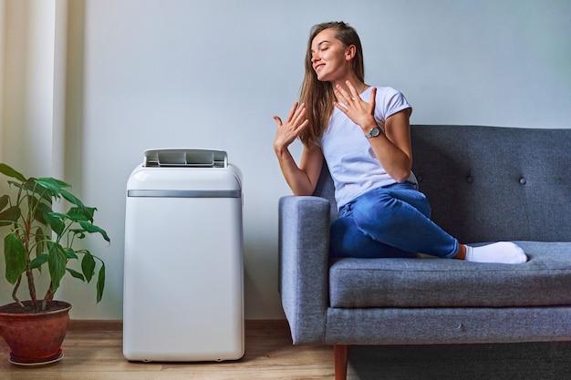 Młoda dorywcza kobieta siedzi na kanapie i używa klimatyzatora podłogowego do chłodzenia w gorące letnie dni. świeże i czyste powietrze w domu