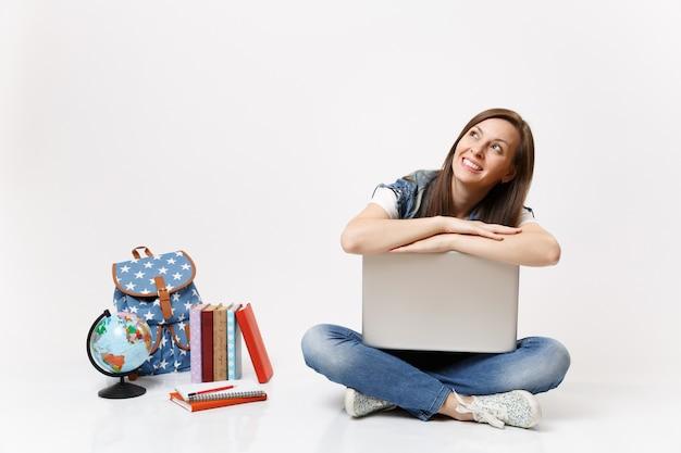 Młoda dorywcza wesoła studentka chuda na laptopie komputer pc, patrząc w górę, marząc, siedząc w pobliżu kuli ziemskiej, plecaka, podręczników szkolnych na białym tle