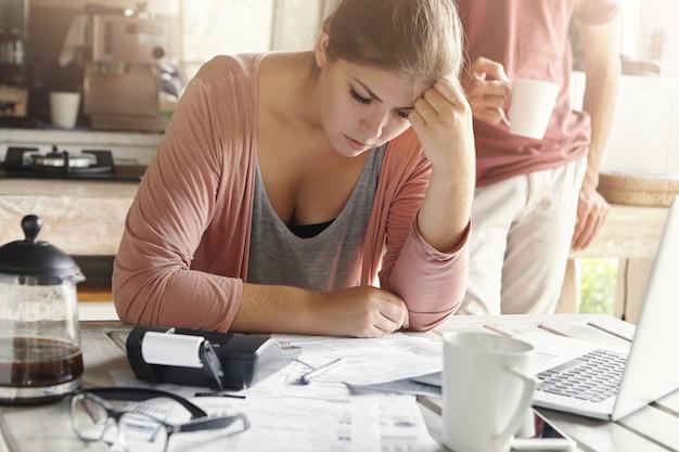 Młoda dorywczo kobieta o przygnębionym wyglądzie, zarządzająca finansami rodzinnymi i robiąca papierkową robotę, siedząca przy kuchennym stole z dużą ilością papierów, kalkulatorem i laptopem