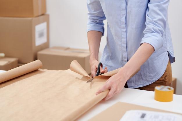 Młoda dorywczo pracownica biura sklepu internetowego do cięcia papieru do pakowania paczek z zamówieniami klientów