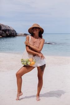 Młoda, dość kaukaska opalona, sprawna kobieta w dzianinowych ubraniach na tropikalnej plaży w słomkowym kapeluszu trzymająca ekologia wielokrotnego użytku torba sznurkowa pełna owoców jabłko pomarańczowe winogrona