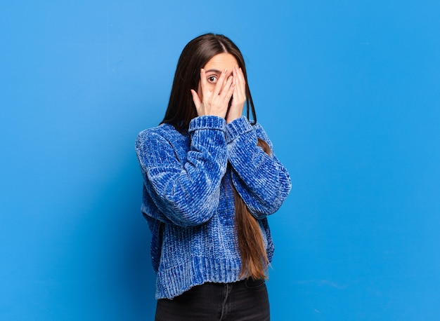 Młoda dość przypadkowa kobieta czująca się przestraszona lub zawstydzona, zerkająca lub szpiegująca z oczami do połowy zakrytymi rękami