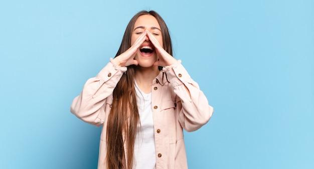 Młoda dość przypadkowa kobieta czuje się szczęśliwa, podekscytowana i pozytywna, krzyczy głośno z rękami przy ustach i woła