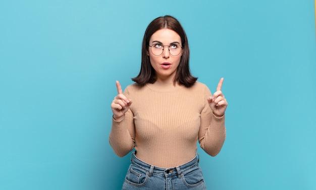 Młoda dość przypadkowa kobieta wyglądająca na zszokowaną, zdumioną i otwartą ustami, wskazująca w górę obiema rękami, aby skopiować przestrzeń