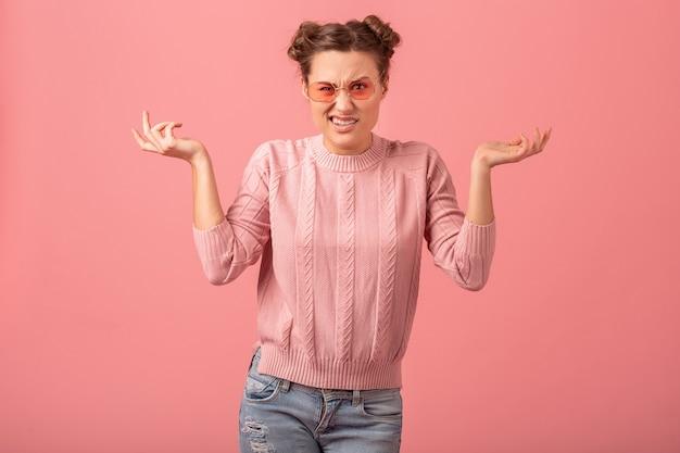 Młoda dość zabawna kobieta ma problem, odczuwa stres, trzyma ręce w różowym swetrze i okularach przeciwsłonecznych na białym tle na różowym tle studia
