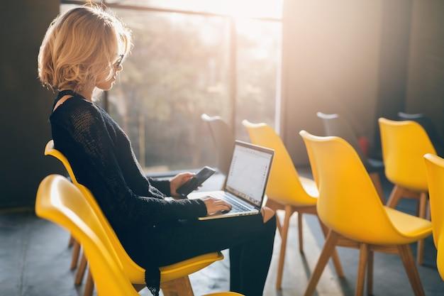 Młoda, dość zajęta kobieta siedzi samotnie w sali konferencyjnej, wiele żółtych krzeseł