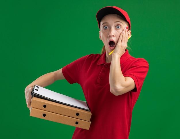 Młoda dostawa dziewczyna w czerwonym mundurze i czapce, trzymająca pudełka po pizzy i schowek z pustymi stronami z ołówkiem zaskoczona