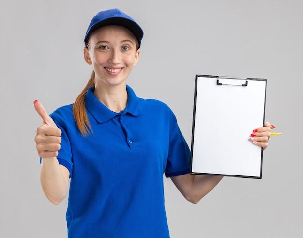 Młoda dostawa dziewczyna w niebieskim mundurze i czapce, trzymając schowek z pustymi stronami, uśmiechając się pewnie pokazując kciuk do góry stojący nad białą ścianą