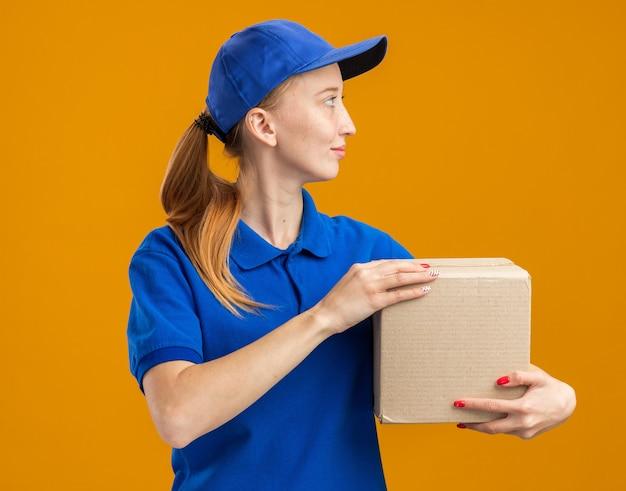 Młoda dostawa dziewczyna w niebieskim mundurze i czapce trzymająca karton patrząc na bok z uśmiechem na twarzy szczęśliwa i pewna siebie stojąca nad pomarańczową ścianą