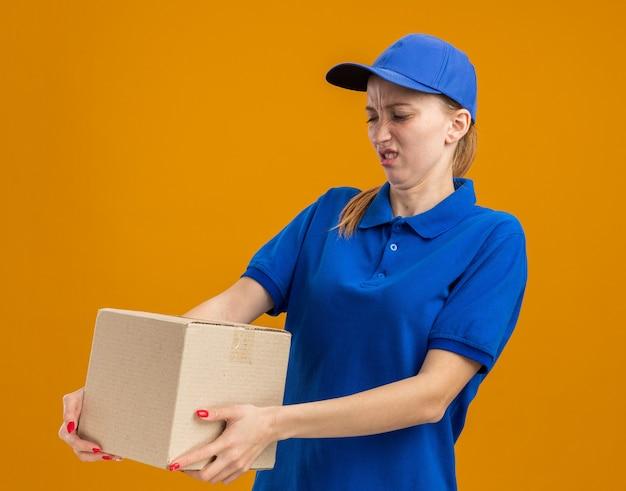 Młoda dostawa dziewczyna w niebieskim mundurze i czapce, trzymająca karton, patrząc na to, że jest zdezorientowana i niezadowolona, stojąc nad pomarańczową ścianą