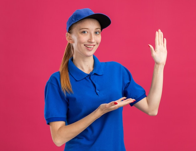 Młoda dostawa dziewczyna w niebieskim mundurze i czapce uśmiecha się pewnie prezentując przestrzeń z ramieniem ręki stojącym nad różową ścianą