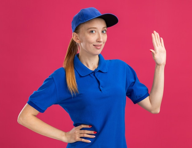 Młoda dostawa dziewczyna w niebieskim mundurze i czapce, uśmiechając się pewnie pokazując otwarte ramię stojące nad różową ścianą