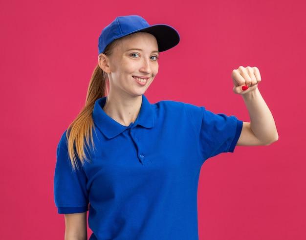 Młoda dostawa dziewczyna w niebieskim mundurze i czapce, uśmiechając się pewnie, szczęśliwa i pozytywnie pokazując pięść stojącą nad różową ścianą