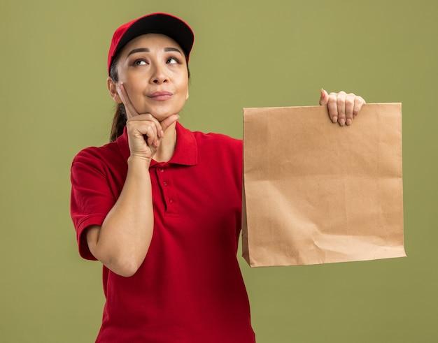 Młoda dostawa kobieta w czerwonym mundurze i czapce trzymająca papierowy pakiet patrząc zdziwiona stojąca nad zieloną ścianą