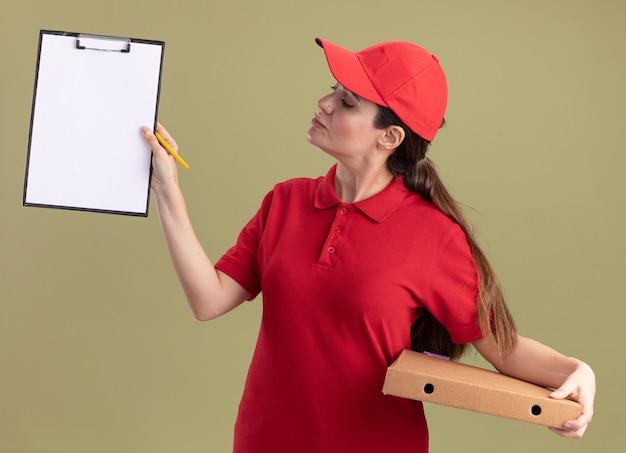 Młoda dostawa kobieta w mundurze i czapce trzymająca paczkę pizzy pokazująca schowek z ołówkiem w dłoni, patrząca na schowek odizolowany na oliwkowozielonej ścianie