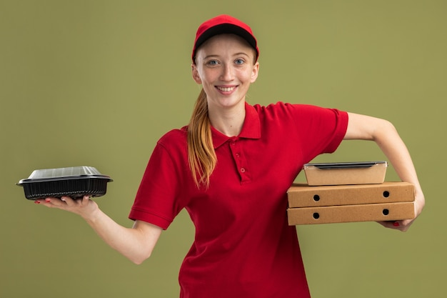 Młoda dostawcza dziewczyna w czerwonym mundurze i czapce, trzymająca pudełka po pizzy i paczki z jedzeniem, uśmiechnięta pewnie nad zieloną ścianą