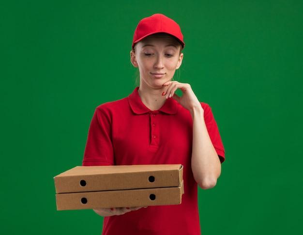 Młoda dostawcza dziewczyna w czerwonym mundurze i czapce, trzymająca pudełka po pizzy, patrząca na nie z ręką na brodzie, myśląca stojąc nad zieloną ścianą