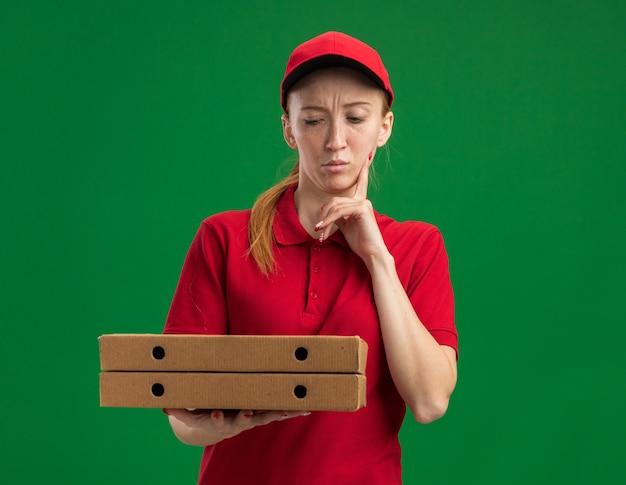 Młoda dostawcza dziewczyna w czerwonym mundurze i czapce trzymająca pudełka po pizzy, patrząca na nie zdziwiona palcem na brodzie, stojąca nad zieloną ścianą