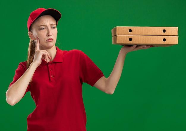 Młoda dostawcza dziewczyna w czerwonym mundurze i czapce trzymająca pudełka po pizzy, patrząca na nie zdziwiona, stojąca nad zieloną ścianą