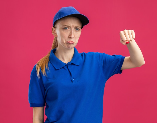 Młoda dostawcza dziewczyna w niebieskim mundurze i czapce ze smutnym wyrazem twarzy zaciskająca usta pokazujące pięść