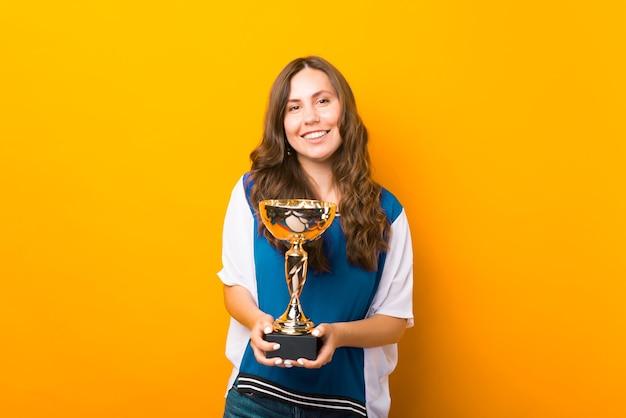 Młoda dumna kobieta trzyma trofeum, które właśnie dostała.