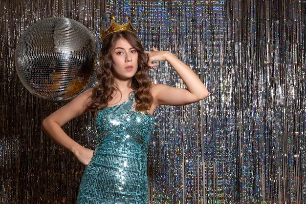 Młoda dumna piękna pani ubrana w niebiesko-zieloną błyszczącą sukienkę z cekinami z koroną na imprezie